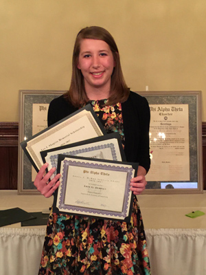 Erin Dempsey smiling with Chapter awards.