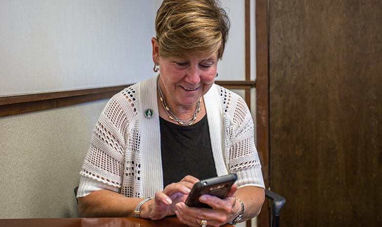 Cheryl Norton logs into twitter account from smart phone