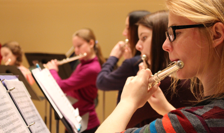 student flute player in college music concert