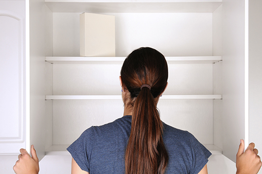 woman in front of an empty cupboard