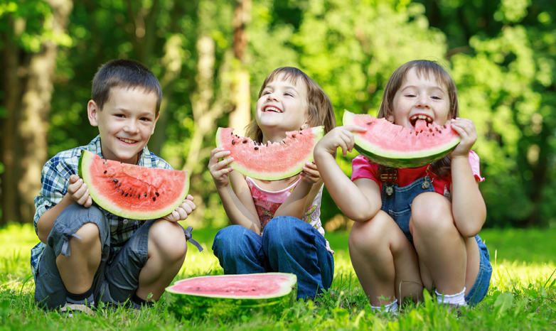 kids eating watermelon in the park