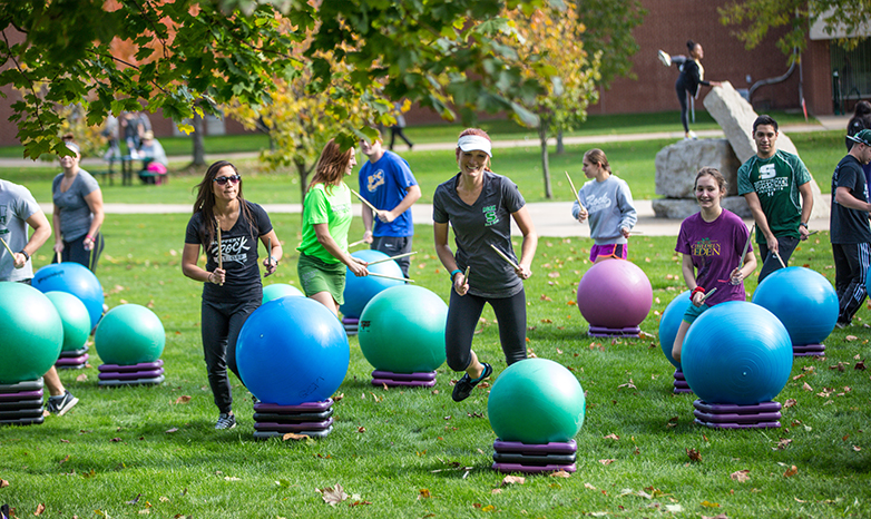 exercise science students drumming with yoga balls