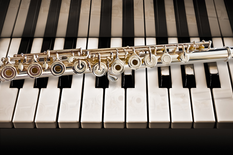 A flute lays on a piano