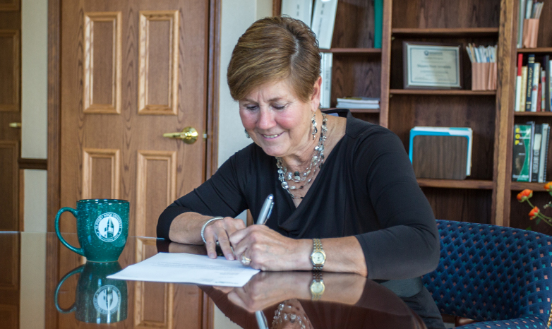 cheryl norton signing a document