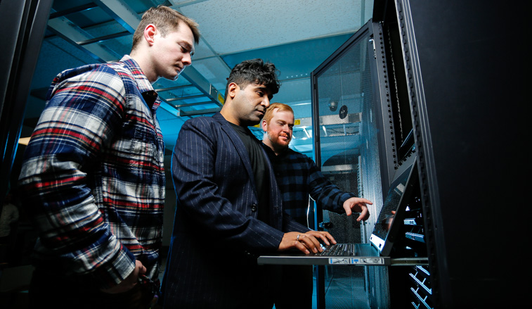 Students and a professor working on a mainframe