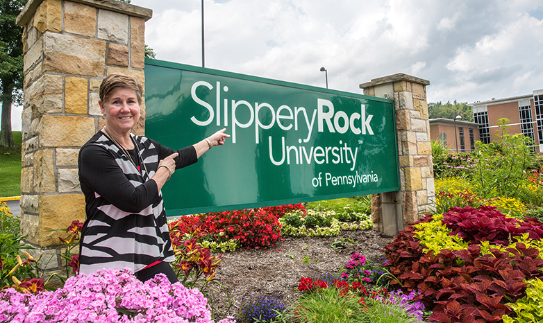 cheryl norton pointing to university sign