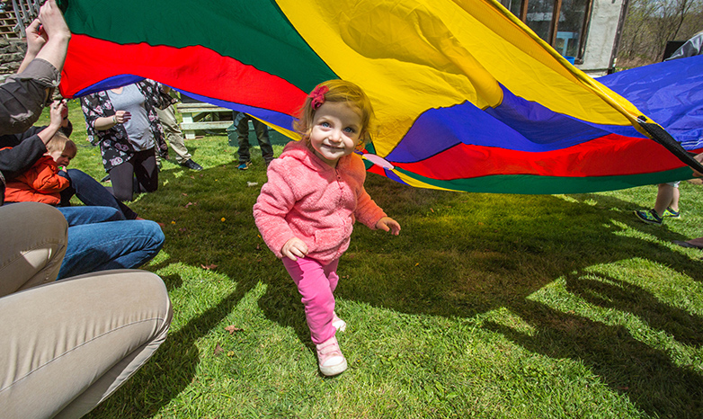 toddler running under colorful parachute during children's festival