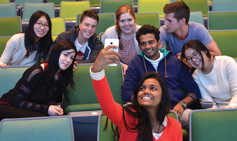 happy students of diversity taking a group selfie
