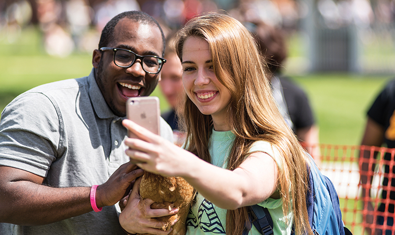 happy students taking a sunny outdoors selfie