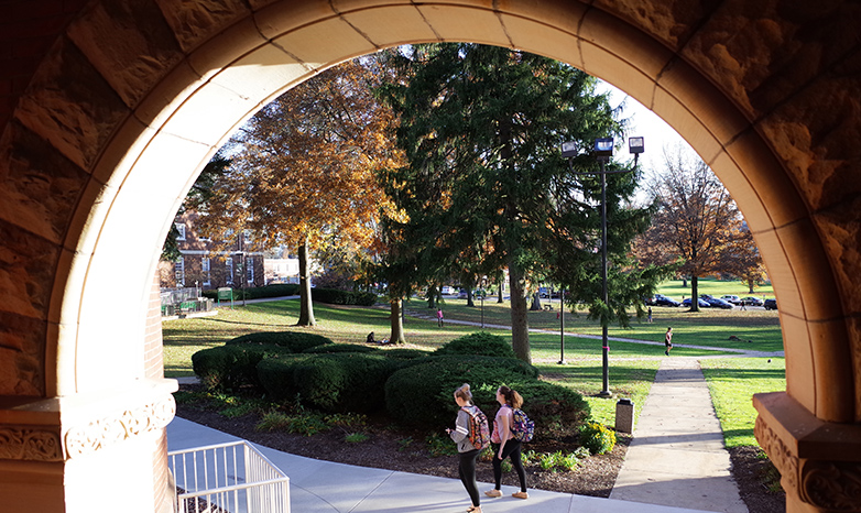 old main arch with students walking past
