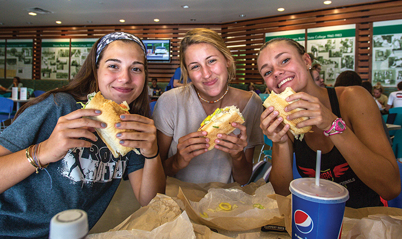 three students eating sub sandwiches