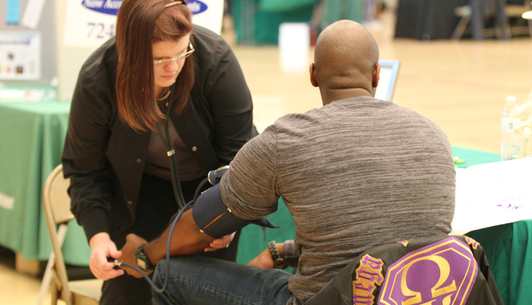 Woman checking man's blood pressure