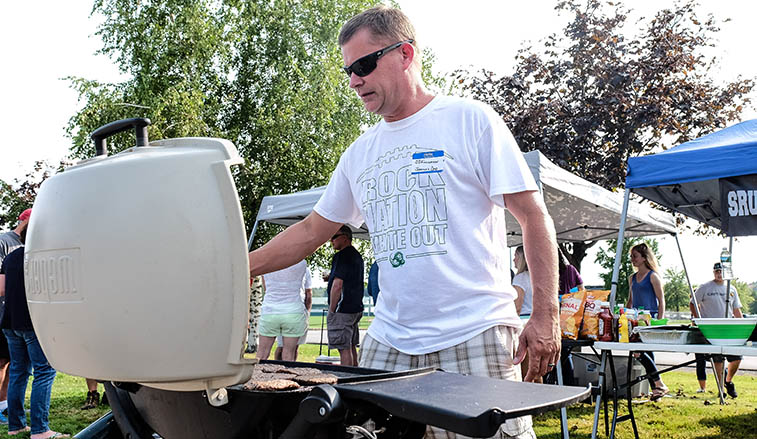 Man grillking burgers at a tailgate