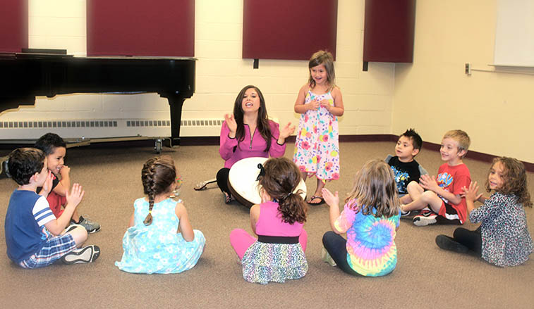 Professor teaching music to pre-school children