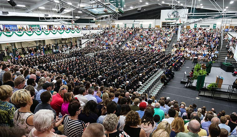 graduates sitting during commencement in the spring