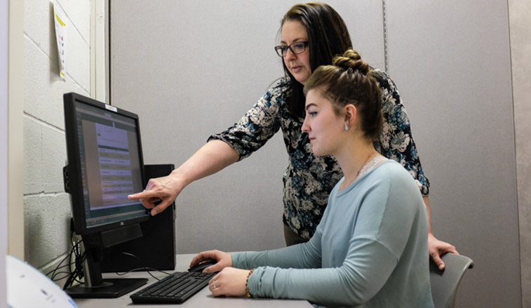 Faculty memeber training a student worker on a computer