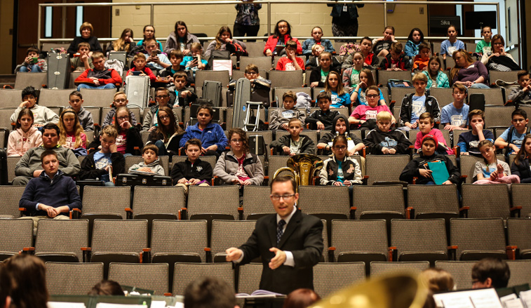 Elementary students watch the wind ensemble