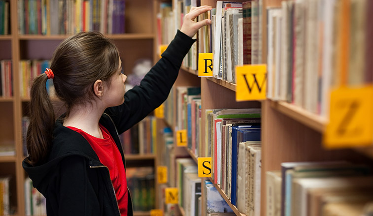 Girl selecting a book in a library