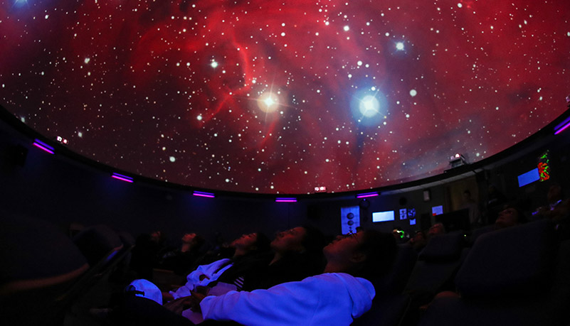 visitors to the planetarium enjoy a show