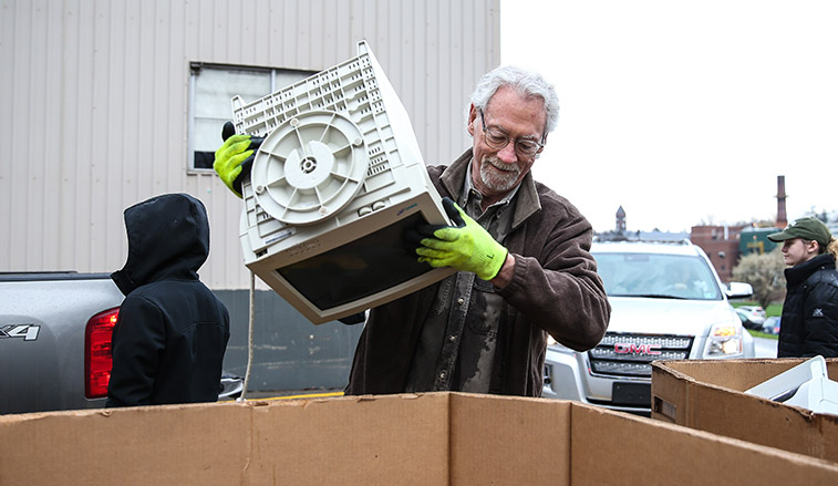 Man recycling an old computer monitor