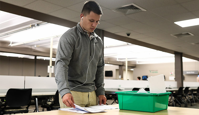 A student sorts through papers that hee has print for his classwork
