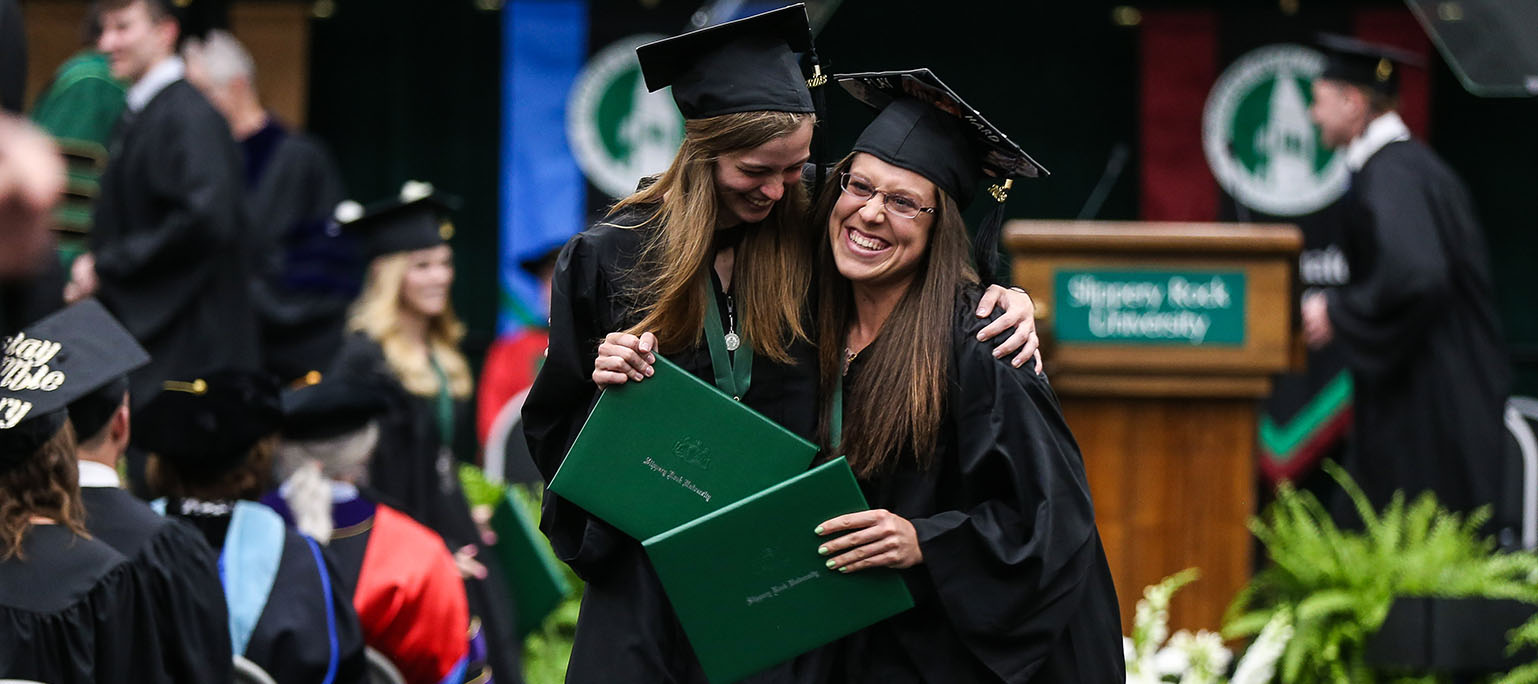 Two graduate hugging after receiving their degrees