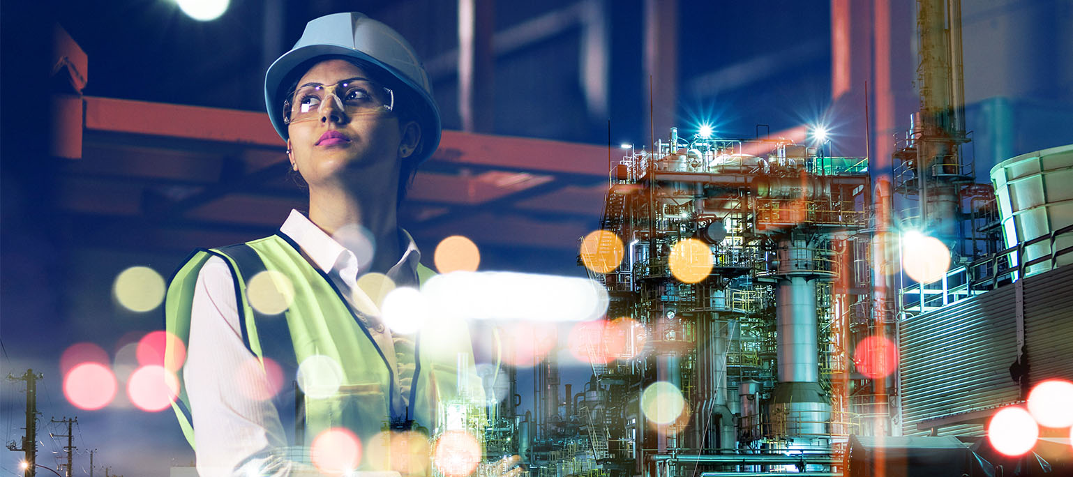 Woman in a safety vest with a hard hat and safety glasses looking at a manutfacturing plant