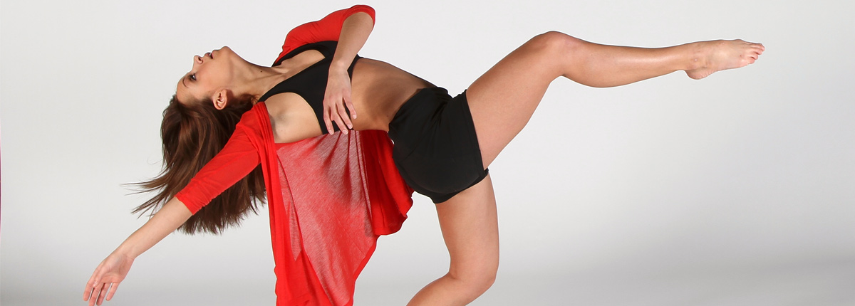 Woman in red shirt poses in dance position with foot in air