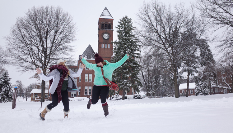 Students jumping with joy in front of old main