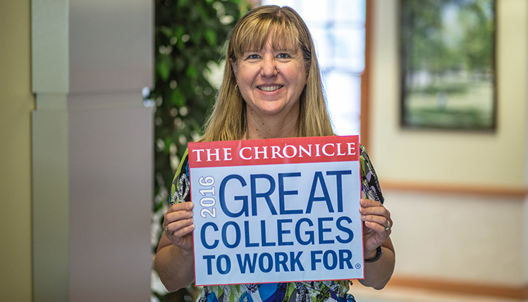 slippery rock university employees hold sign depicting great colleges to work for logo