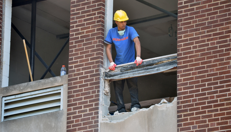 Worker removing brick from Spotts south wall