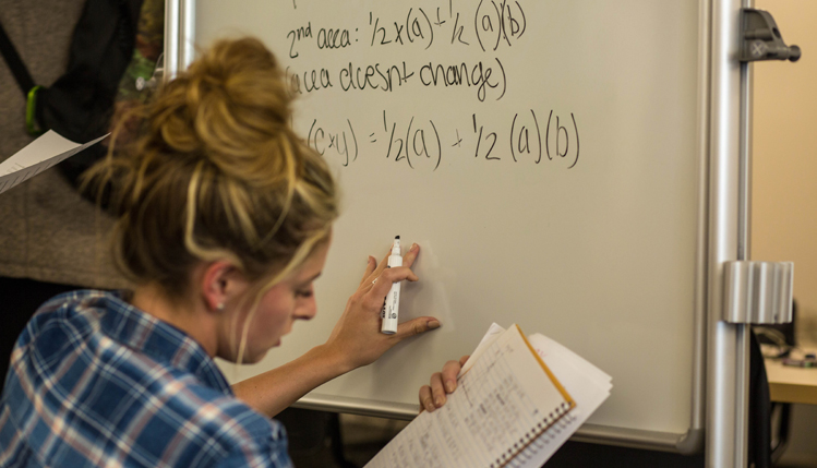 Student writes on dry-erase board