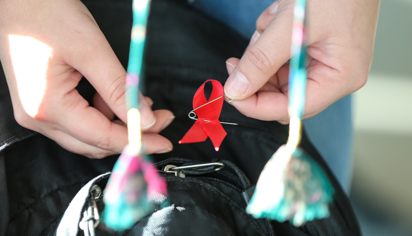 Woman placing an AIDS pin