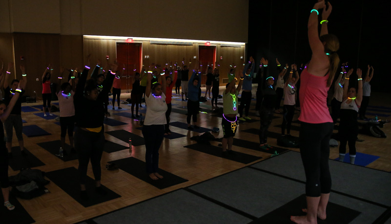 Students wearing glow sticks while doing yoga