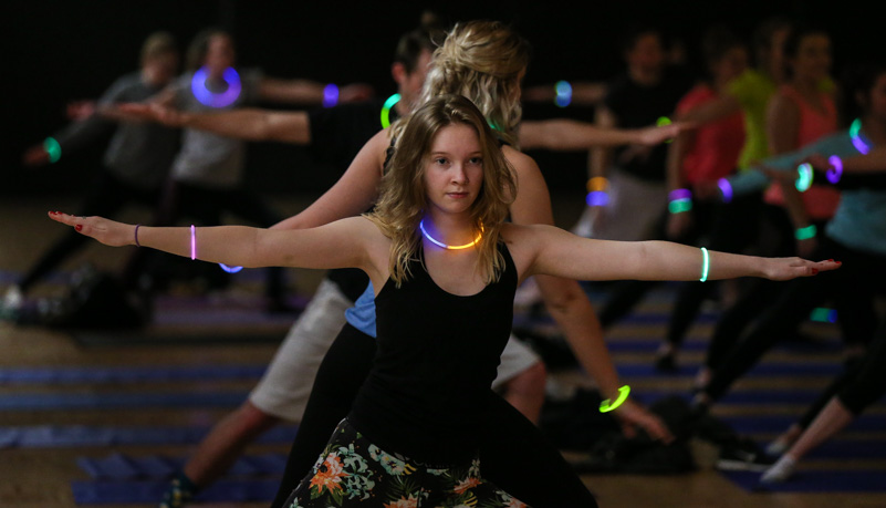 A woman doing yoga and wearing glow sticks