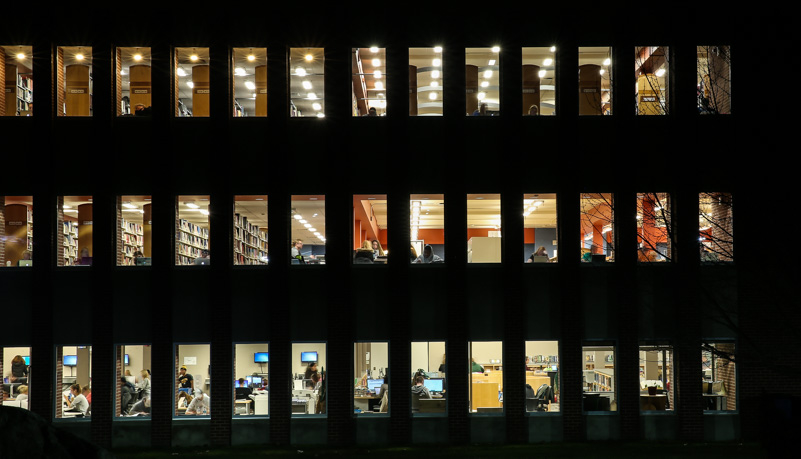 Students studying in the library after dark