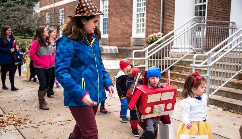 Group of kids walking on sidewalk dressed in Halloween costumes