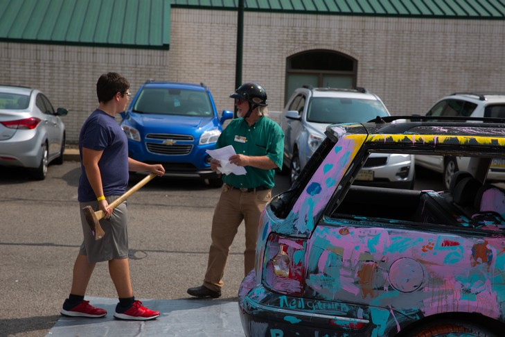 kid gets ready to hit car with axe
