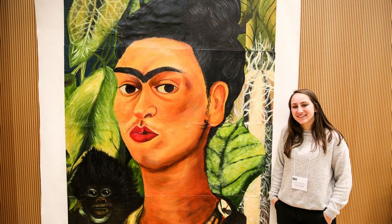 Student standing next to Frida Kahlo portrait