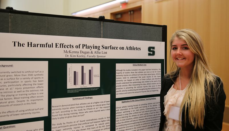 Girl presenting findings on the harmful effects of playing surface on athletes