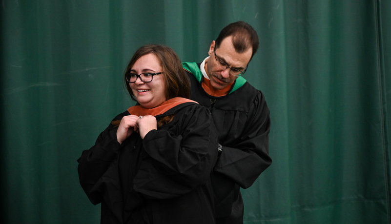 Graduate gets help with her hood