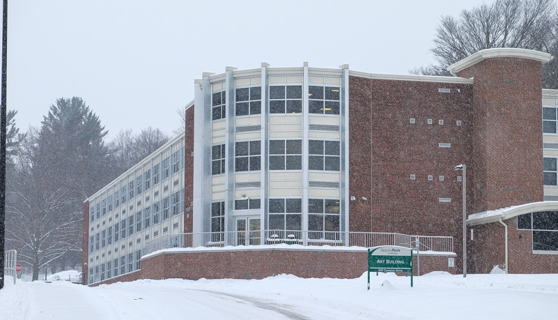Rhoades Hall through the trees and snow