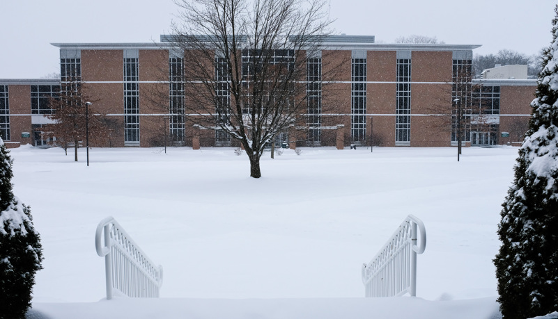 Science building through the trees and snow