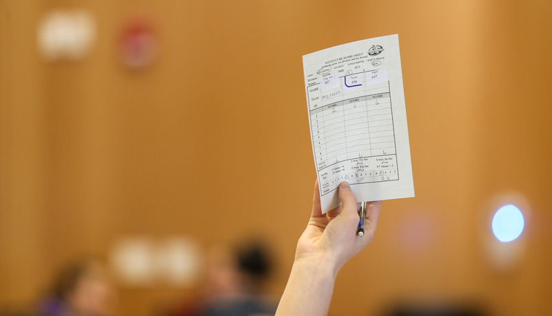 Student holding up a score card