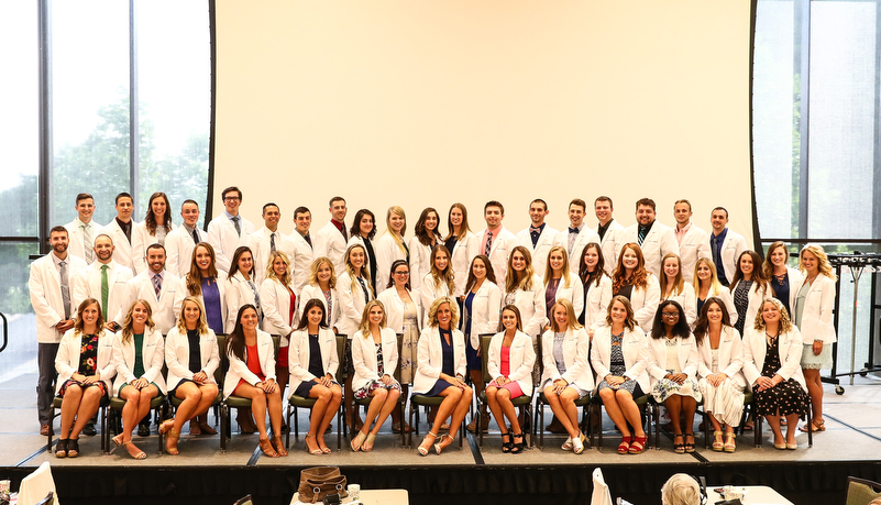 Group photo of the class with their white coats