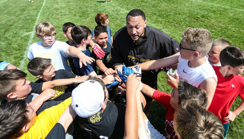 Charlie Batch with kids in a huddle