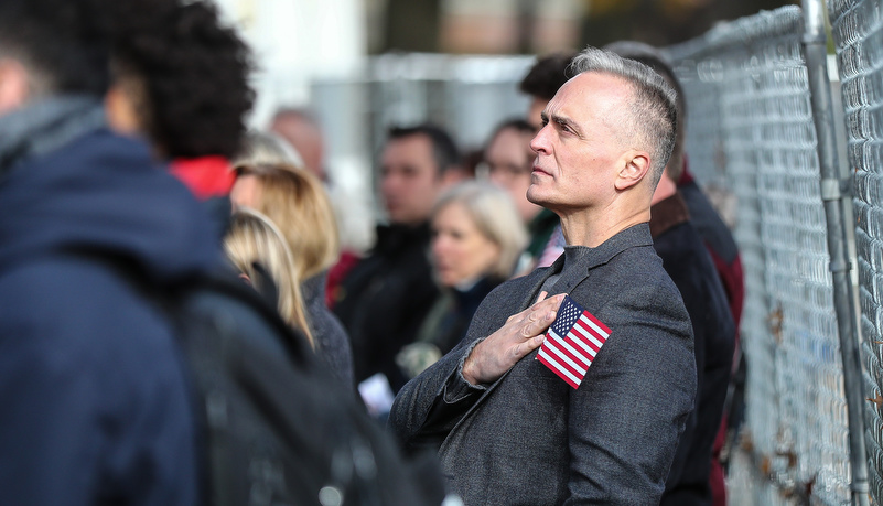 Man with his hand over his heart with an American flag