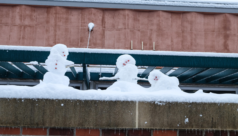 Three snow men on a ledge