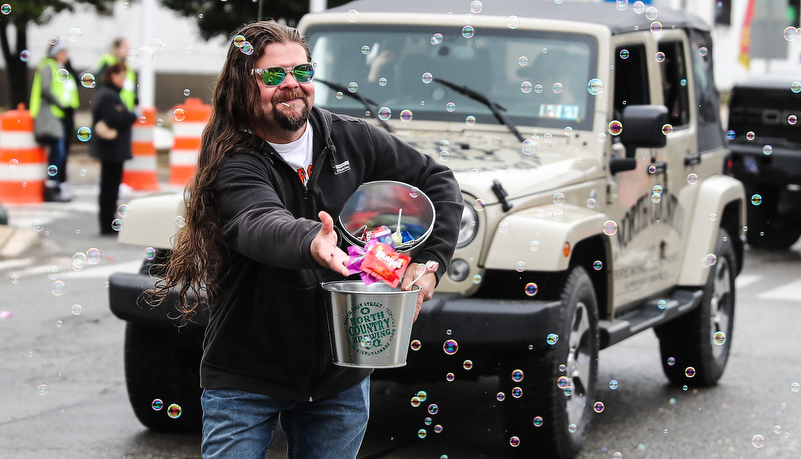 man in parade throwing candy