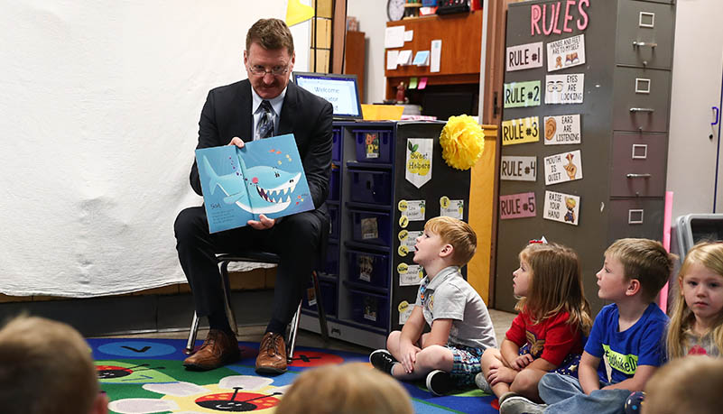 Man reading to pre school students